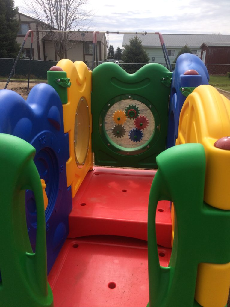 Inside of play equipment showing off multi-colored pieces and cogs