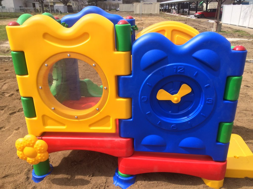 Side of play equipment for young children with a viewing window and a moveable clock