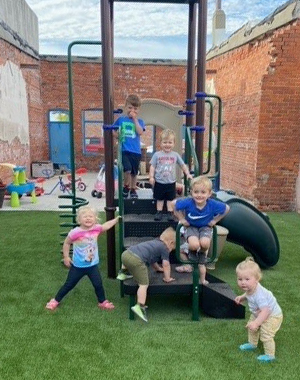 Children playing in updated play space. Playground upgrade artificial turf surfacing installation playground equipment