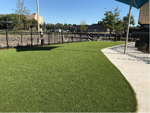 View of artificial turf installed near a commercial area.
