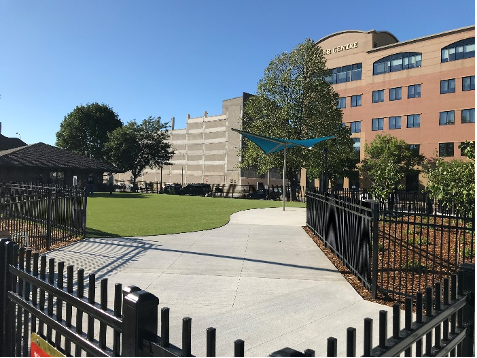 Sidewalk corner view of the finished installation of artificial turf and ornamental fencing.