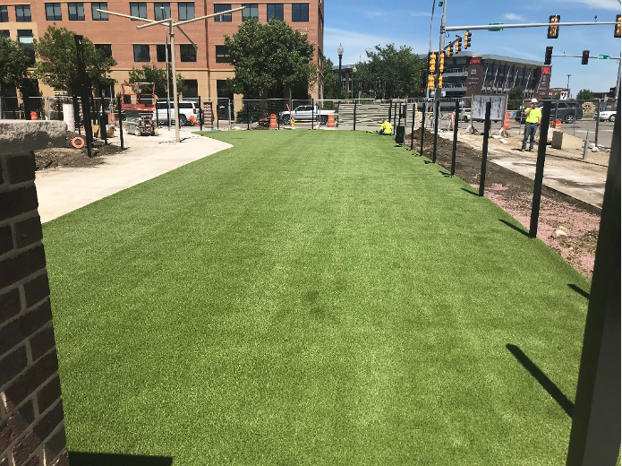 Artificial turf and ornamental fence being installed for a commercial dog park.