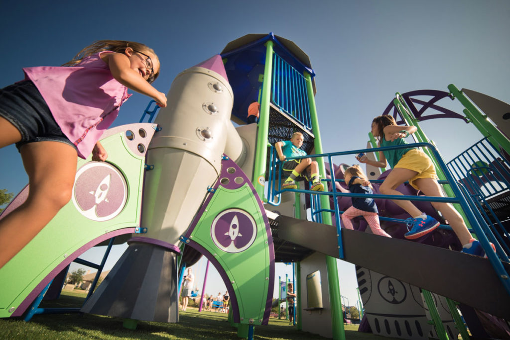 Children actively playing on rocket-themed playground