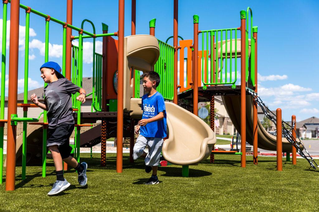 Two boys racing around a playground