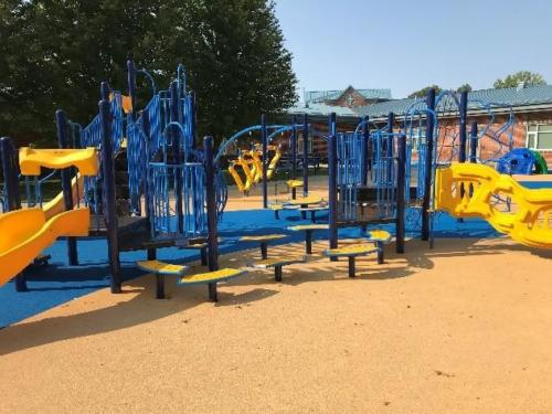 Blue and yellow playground structure on pour-in-place unitary surfacing.