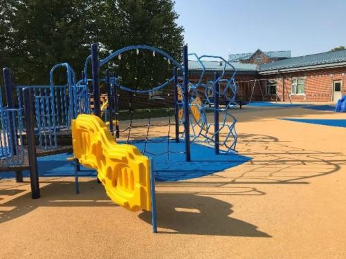 Angled view of a blue and yellow playground structure on pour-in-place unitary surfacing.