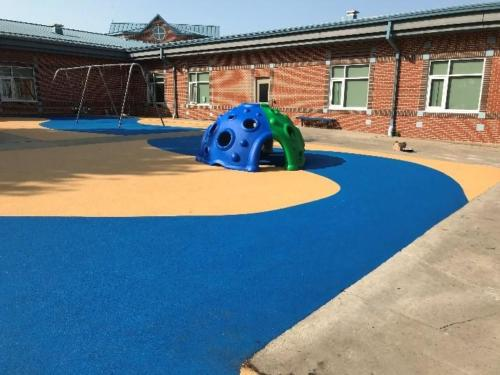 Swings and climbing structure atop tan and blue pour-in-place rubber unitary surfacing.