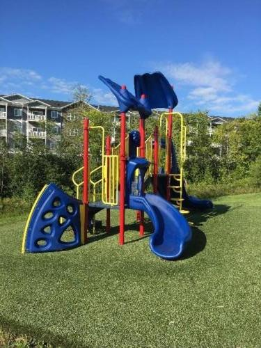 Commercial playground structure (back view) and artificial turf surface - Pine Apartments
