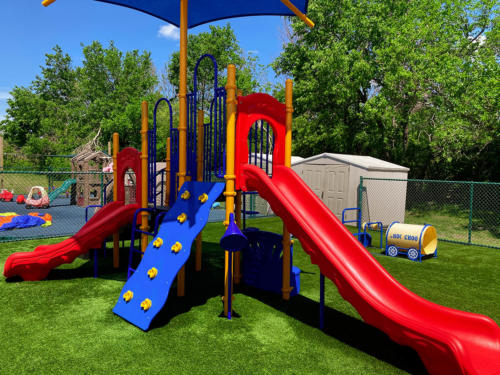 Commercial play structure with slides, climbing element, and shade for Whistle Stop Academy.