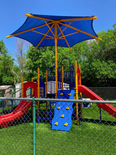 Side view of a commercial play structure with slides, climbing element, and shade for Whistle Stop Academy.